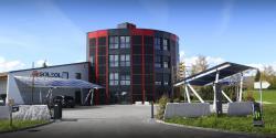 Gesamtansicht des Erneuerbare-Energie-Kraftwerks der Soleol SA mit den PV-Paneelen überdachten Parkplätze. Das Gebäude produziert gesamthaft 234'700 kWh/a Solarenergie.