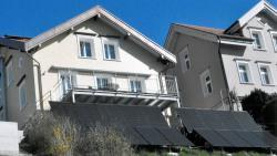 Die Südfassade des sanierten PEB-EFH. Die PV-Anlage steht wegen Platzmangels an einer Stützmauer und auf dem Wiesenbord statt wie die Solarkollektoren auf dem Dach. Total werden 6'000 kWh/a erzeugt.