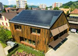Die Eichenschalung des Gebäudes aus Schweizer Holz wurde mit Eisenpulver behandelt. Dadurch entstand die dunkle, rostige Färbung.