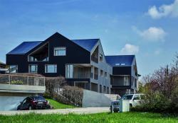 Südwestansicht des energieautarken MFH in Brütten/ZH. Die 126.5 kW starke dach- und fassadenintegrierte PV-Anlage ist optimal ganzflächig integriert und produziert 92'000 kWh/a.