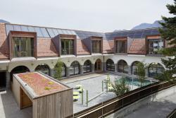 Innenhofansicht des sanierten Gebäudekom-plexes mit DWHG und Doppelkindergarten mit Baujahr 1914 und einem Energiebedarf von 29'400 kWh/a.
