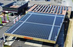 Die perfekt integrierte 168 kW starke Parkplatzanlage im Vordergrund und die aufgeständerte 84 kW starke Anlage auf der Filiale im Hintergrund decken den Gesamtenergiebedarf des Supermarkts (198'900 kWh/a) zu 135% und versorgen das angrenzende Restaurant Chickeria mit Strom.
