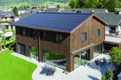 Die 29 kW starke, ganzflächig dachintegrierte PV-Anlage harmoniert mit der Holzfassade aus Weisstanne.