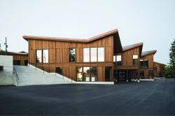Die PlusEnergie-Schule besticht mit ihrer dunkelbraunen Fassade aus Weisstannenholz