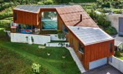 Das PEB-EFH Bottinelli-Croce in Cugnasco/TI mit seinen drei Fassadenelementen Holz, Metall und PV-Anlage bettet sich harmonisch in die Landschaft der Magadinoebene ein.