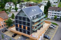 Südwestansicht des neu erstellten MFH Chrüzmatte in Aesch/LU. Es deckt mit dach- und dezent südwestlich fassadenintegrierten Solaranlagen 50% des Gesamtenergiebedarfs.