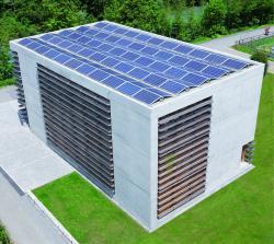 Gesamtansicht des Bürogebäudes in Ilanz/GR mit der 28.6 kW starken, ganzflächig seitenbündig integrierten Ost-West-PV-Flachdach-Anlage, die jährlich 30'000 kWh produziert.