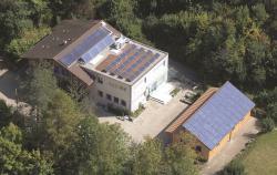 Das Gebäude Büschiheim in Köniz/BE. Links im Bild ist die teilweise aufgeständerten 39 m2 grosse Sonnenkollektoranlage, auf dem Flachdach die aufgeständerte PV-Anlage Büschi II mit 5.4 kWp zu sehen,  und rechts im Bild ist die sorgfältig ganzflächig integrierte PV-Anlage Büschi I mit 10.4 kWp.